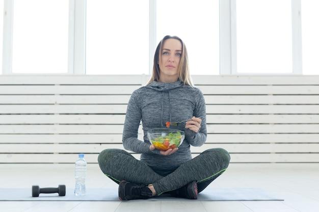Concepto de deporte, estilo de vida saludable y personas - mujer joven con ensalada y una pesa sentada en el suelo