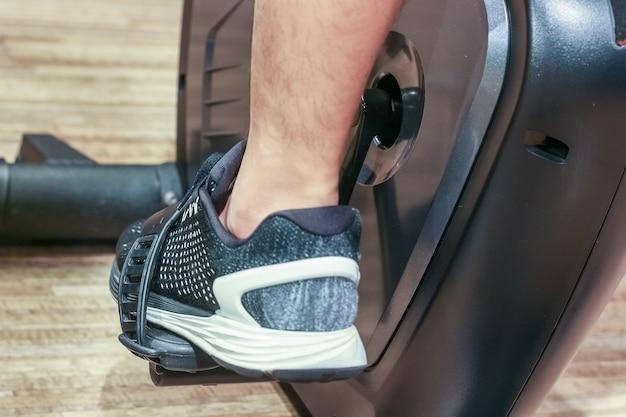 Concepto de deporte, fitness, estilo de vida, tecnología y personas - cerca de las piernas de los hombres en bicicleta en el gimnasio