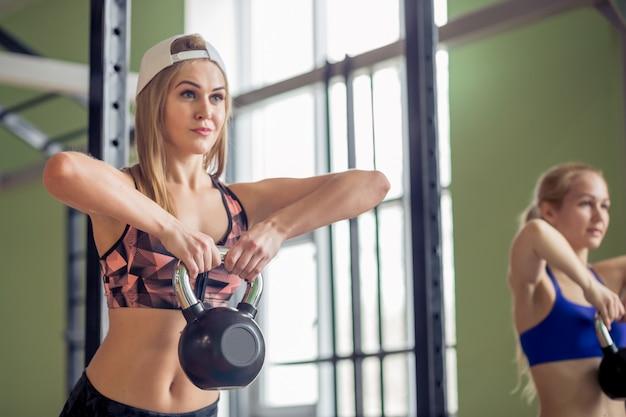 Concepto de deporte, fitness, levantamiento de pesas y entrenamiento. grupo de personas con pesas rusas y rastreadores de frecuencia cardíaca haciendo ejercicio en el gimnasio