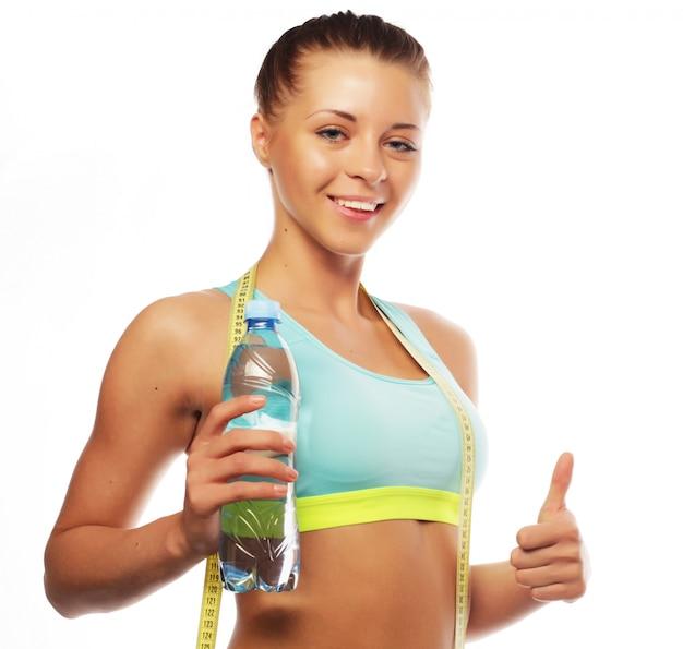 Concepto de deporte, fitness y personas: joven mujer sonriente feliz en ropa deportiva con agua,