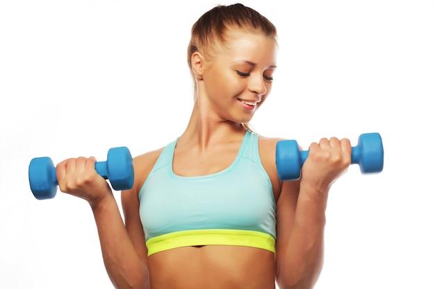 Concepto de deporte, fitness y personas: mujer en la práctica de equipos deportivos con pesas de mano aisladas sobre fondo blanco