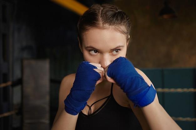 Concepto de deporte, lucha, entrenamiento y ejercicio físico. filmación en interiores de concentrada joven mujer caucásica vistiendo top y vendas apretando los puños