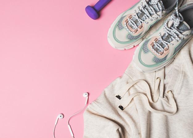 Concepto de deporte, saludable y moda en rosa con zapatillas, sudadera con capucha y auriculares.