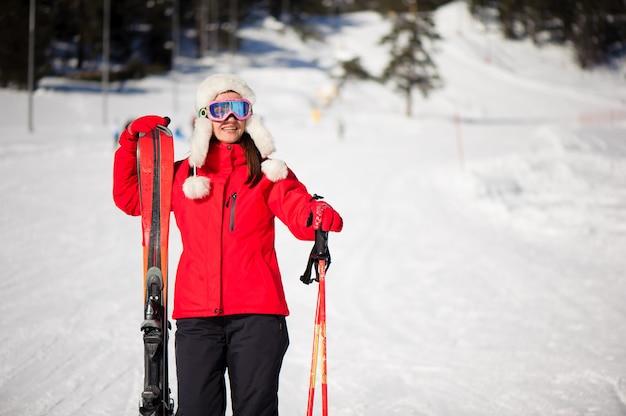 Concepto de deporte y vacaciones de invierno con mujer con esquís en sus manos al pie de la montaña