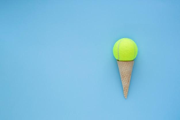 Concepto de deporte de verano de tenis. pelota de tenis amarilla en cono de helado sobre fondo azul. espacio libre para texto.
