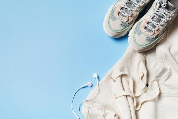 Concepto deportivo, saludable y moda en azul con zapatillas, sudadera con capucha y auriculares.