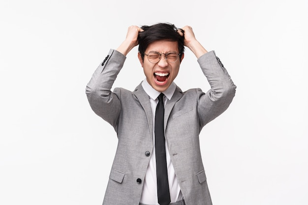 Concepto de depresión, personas y emociones. retrato en la cintura de un joven asiático tenso y estresado con traje formal, corbata, arrancarse el cabello de la cabeza y gritar molesto, de pie en la pared blanca