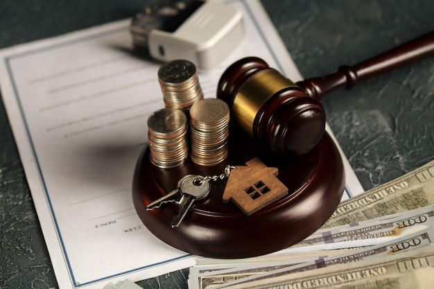 Concepto de derecho inmobiliario. maqueta de madera de casa, monedas y mazo de juez.