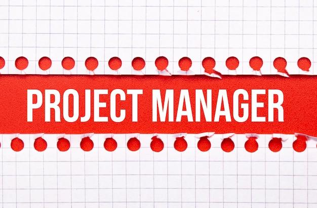Concepto de derecho y negocios. entre dos hojas de cuaderno sobre un fondo rojo la inscripción proyecto gestor