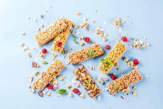Concepto de desayuno y merienda saludable granola casera con frambuesas frescas y nueces y barras de granola sobre fondo azul brillante de patrones sin fisuras