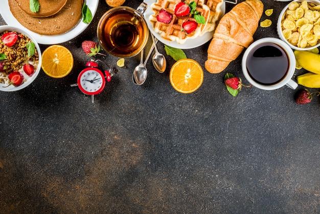 Concepto de desayuno saludable, varios alimentos de la mañana: panqueques, waffles, sándwich de avena con croissant y granola con yogur, fruta, bayas, café, té, fondo de jugo de naranja