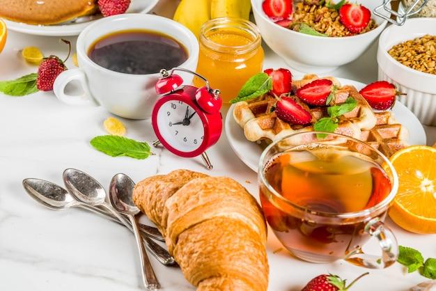 Concepto de desayuno saludable, varios alimentos de la mañana: panqueques, waffles, sándwich de avena con croissant y granola