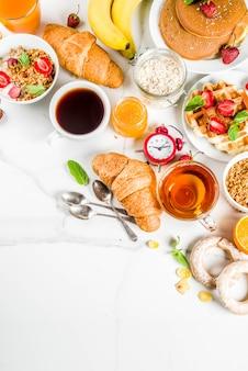 Concepto de desayuno saludable, varios alimentos de la mañana: panqueques, waffles, sándwich de avena con cruasanes y granola con yogur, fruta, bayas, café, té, jugo de naranja, d