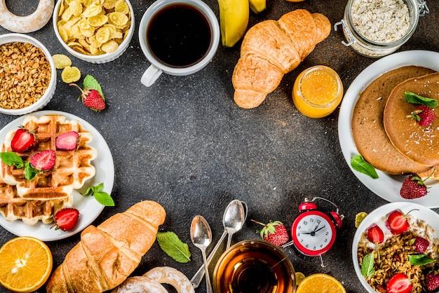 Concepto de desayuno saludable, varios alimentos de la mañana: panqueques, waffles, sándwich de avena con cruasanes y granola con yogur, fruta, bayas, café, té, jugo de naranja