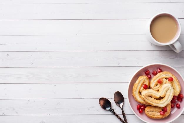 Concepto de desayuno de san valentín. taza de café y galletas corazones en una mesa blanca. copia espacio, plano.