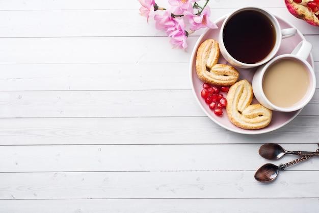 Concepto de desayuno de san valentín. taza de café y galletas corazones en una mesa blanca dos personas. copia espacio, plano.