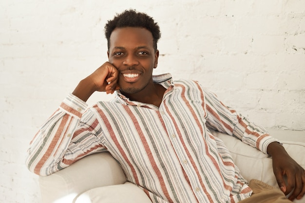 Concepto de descanso, ocio y relajación. fresco carismático joven afroamericano en ropa casual relajante en casa