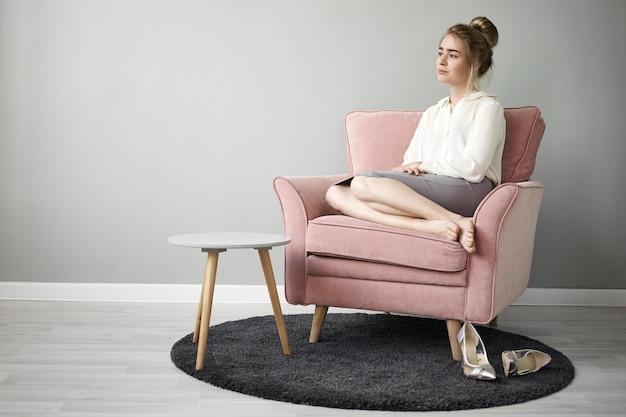 Concepto de descanso, recreación, comodidad y relajación. retrato de un hermoso joven empresario tranquilo vistiendo blusa blanca y falda relajándose en un sillón y mirando a la distancia, con mirada pacífica