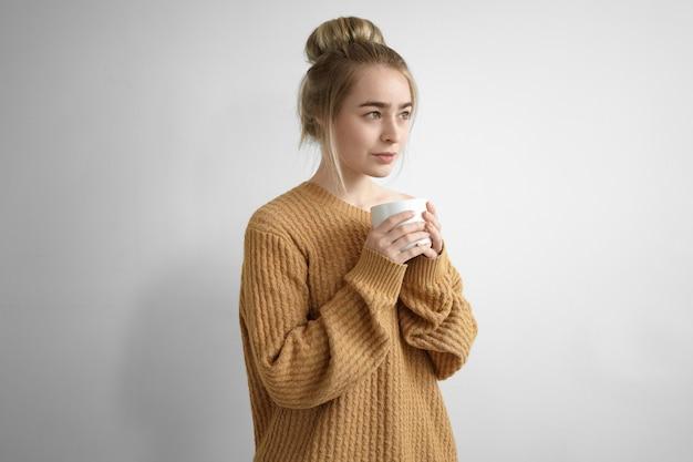 Concepto de descanso y relajación. hermosa joven vistiendo un jersey de gran tamaño manteniendo los ojos cerrados y sosteniendo una taza grande con ambas manos, bebiendo chocolate caliente o café en el interior, sonriendo con alegría
