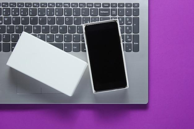 El concepto de desembalaje, blogs de tecno. caja con nuevo teléfono inteligente, portátil en superficie morada.
