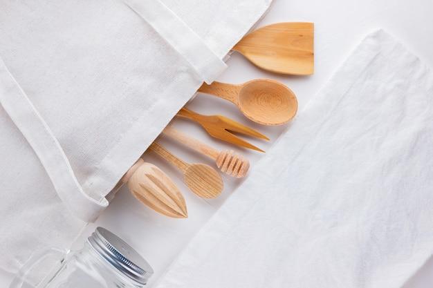 Concepto de desperdicio cero. bolsa ecológica de algodón, tarro de cristal y cubertería de madera. concepto libre de plástico