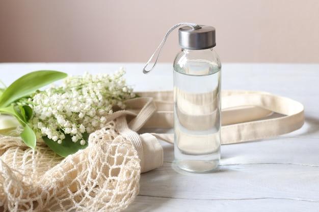Concepto de desperdicio cero. botellas de agua de vidrio y bolsa ecológica sobre una mesa de madera blanca.