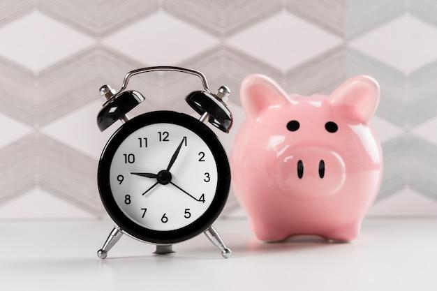 Concepto de despertador y hucha para ahorrar tiempo