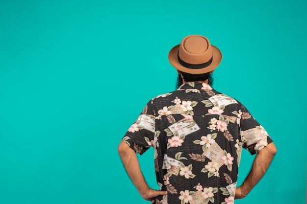 Concepto detrás de los turistas masculinos con un sombrero en un azul.