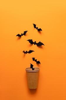 El concepto del día de fiesta de halloween de palos negros vuela de la taza de papel en superficie anaranjada