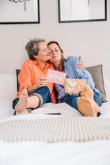 Concepto para el día de la madre en dormitorio con abrazo