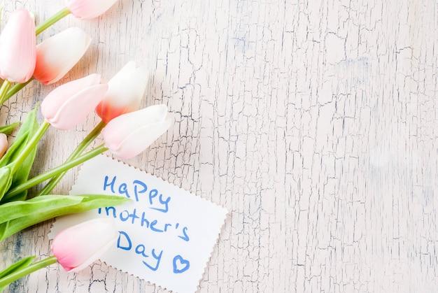 Concepto del día de la madre, fondo de la tarjeta de felicitación. flores tulipanes y nota de saludo feliz día de la madre