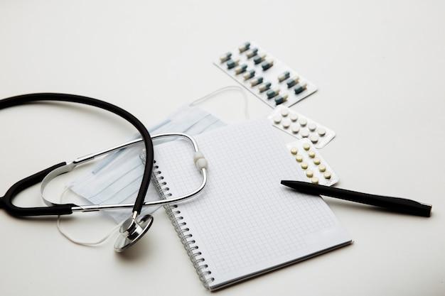 Concepto del día del médico, un estetoscopio, mascarilla, medicamentos y bloc de notas en la mesa del médico o el escritorio de la enfermera.