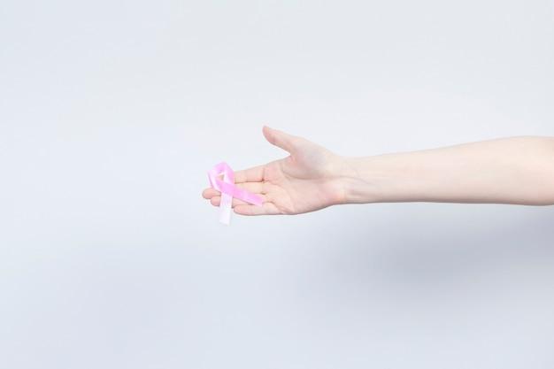 Concepto del día mundial del cáncer de mama. la mujer sostiene la cinta rosada en la mano. octubre mes de concientización sobre el cáncer de mama