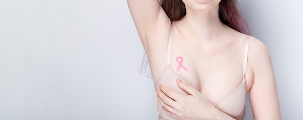 Concepto del día mundial del cáncer de mama. mujer en sujetador con cinta rosa pintada en el pecho. octubre mes de concientización sobre el cáncer de mama. copia espacio