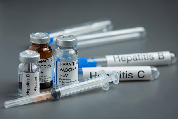Concepto del día mundial de la hepatitis con herramientas médicas y píldoras colocadas sobre una superficie gris