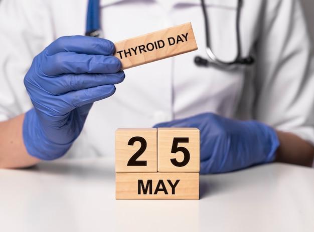 Concepto del día mundial de la tiroides. 25 de mayo en cubos de madera.