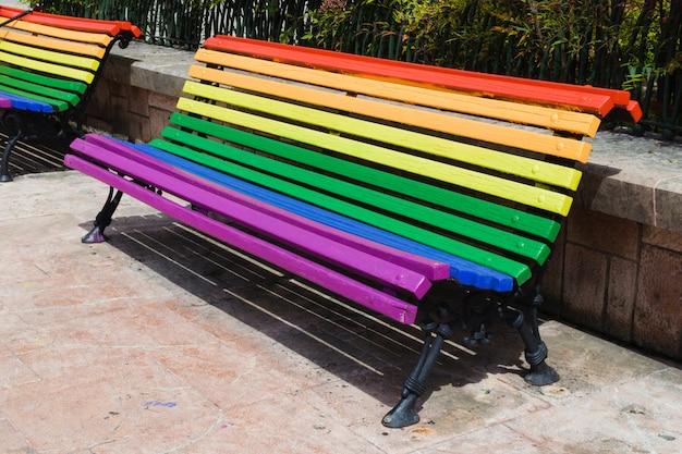 Concepto del día del orgullo. banco de madera pintado en colores del arco iris en un parque