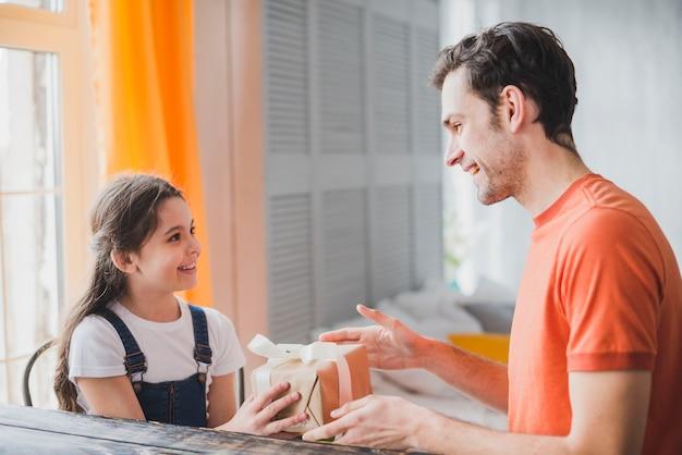 Concepto para el día del padre con hija dando caja de regalo