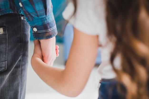 Concepto para el día del padre con padre e hija cogiéndose las manos