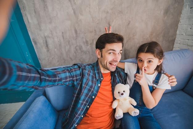 Concepto para el día del padre con padre e hija haciendo selfie