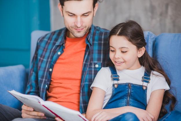 Concepto para el día del padre con padre e hija leyendo