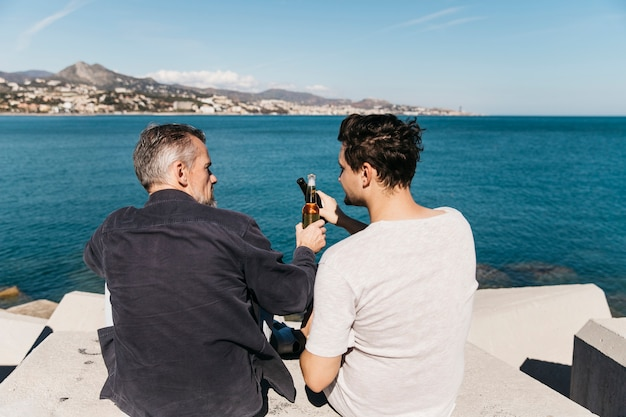 Concepto del día del padre con padre e hijo brindando con cerveza enfrente del océano