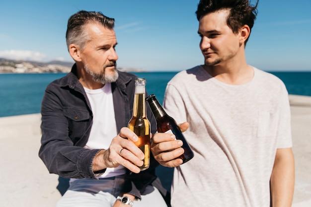 Concepto del día del padre con padre e hijo brindando con cerveza