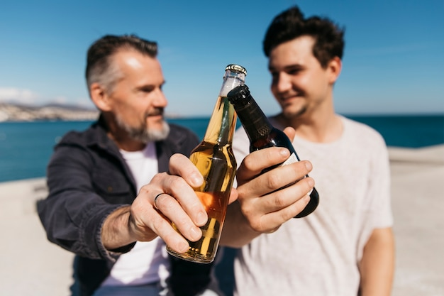 Concepto del día del padre con padre e hijo felices brindando con cerveza