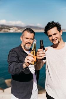 Concepto del día del padre con padre e hijo mostrando cerveza