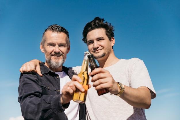 Concepto del día del padre con padre e hijo posando con cerveza