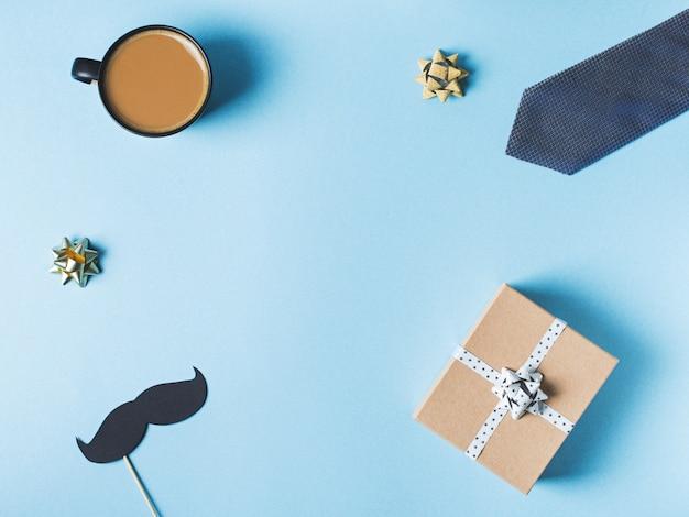 Concepto del día de padres con caja de regalo, corbata y bigote sobre fondo azul