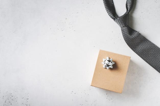 Concepto del día de padres con caja de regalo y corbata sobre fondo blanco