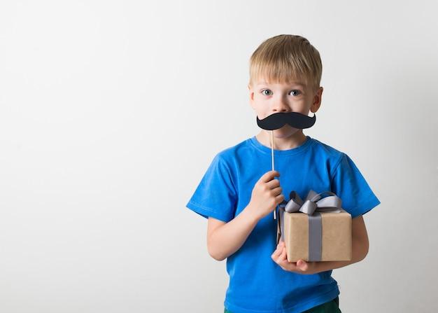 Concepto del día de padres, niña caucásica sonriendo con bigote sobre fondo blanco
