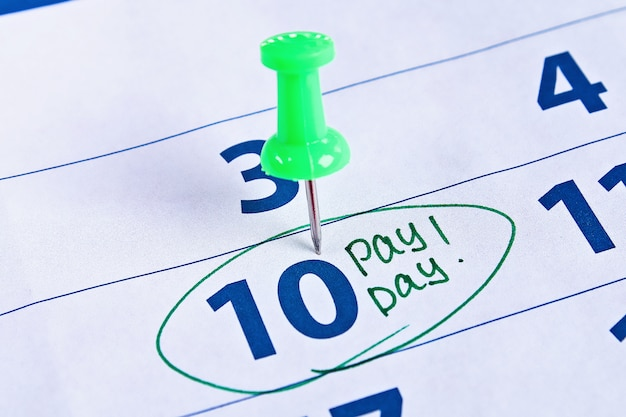 Concepto de día de pago negocios, finanzas, ahorro de dinero. calendario con círculo marcador en día de pago de la palabra
